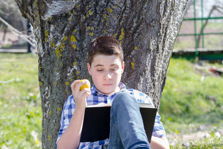 Young boy reading a book in the woods with shallow depth of field and copy space photo