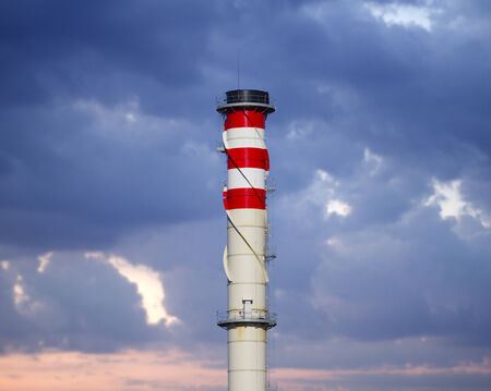 industrial chimneys on cloudy sky at sunset photo