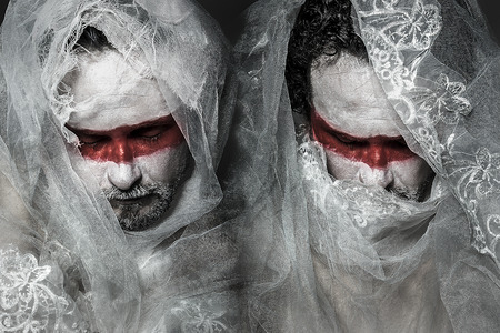man covered with white lace veil, mask of red makeup photo