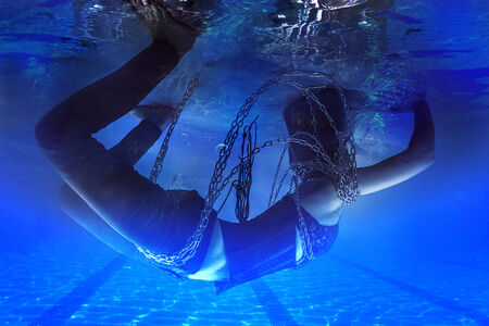 Chained woman underwater, nightmare concept photo