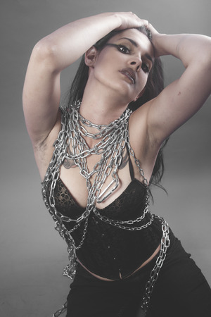 Beautiful brunette woman with big silver chains chained photo
