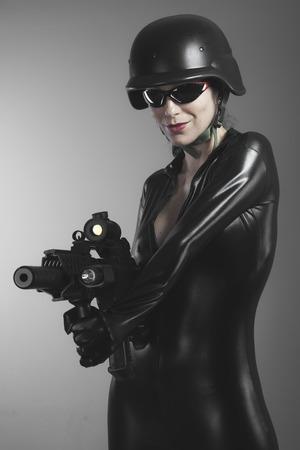 Fire, Brunette woman with enormous bulletproof vest and gun photo