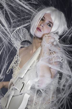 beautiful woman with couture gown in white, violin, music concept photo