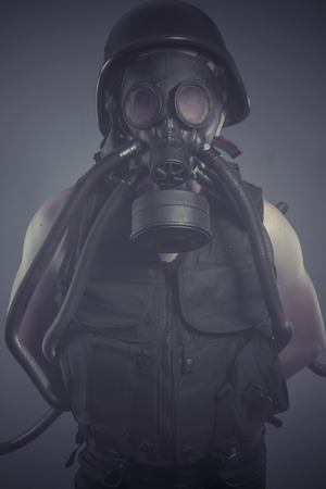 Soldier, Man with black gas mask, pollution concept and ecological disaster photo