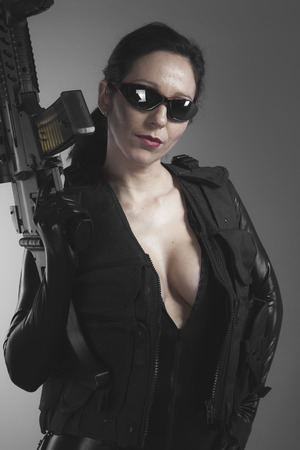 Brunette woman with enormous bulletproof vest and gun photo