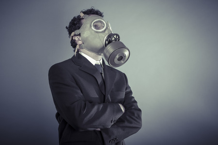 Danger, Business man wearing a gask mask, pollution concept photo
