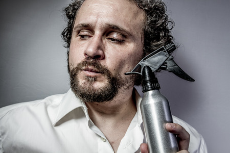 cleaning spray, man with intense expression, white shirt photo
