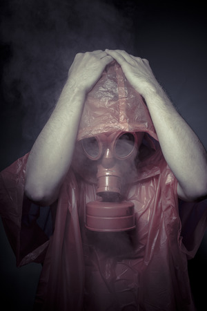 Gas, nuclear disaster, man with red mask and plastic suit photo