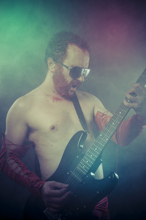 Heavy, rocker man with electric guitar in a rock concert photo