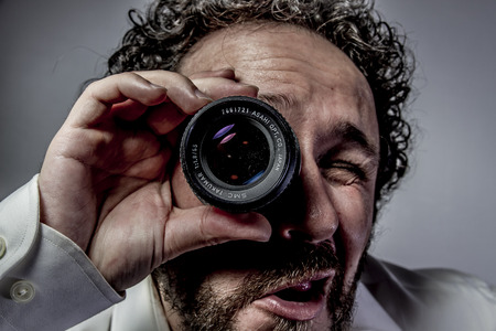 photographer with lens, man with intense expression, white shirt photo