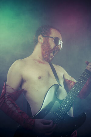rocker man with electric guitar in a rock concert photo