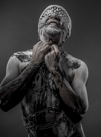 man with chains and blindfolded concept of prison, without freedom photo