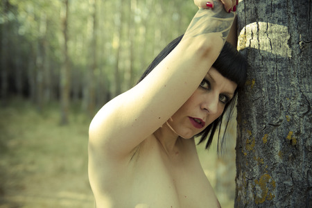 Sensual nude brunette woman in a green forest photo