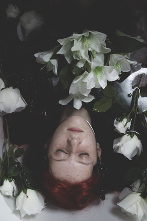 corpse flower: Relaxing, Teen submerged in water with white roses, romance scene