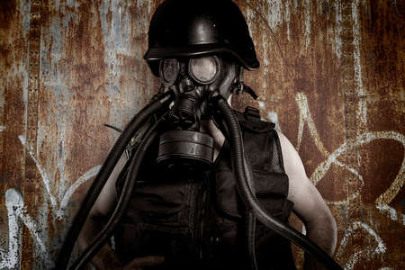 Man with gas mask over dirty texture iron wall photo