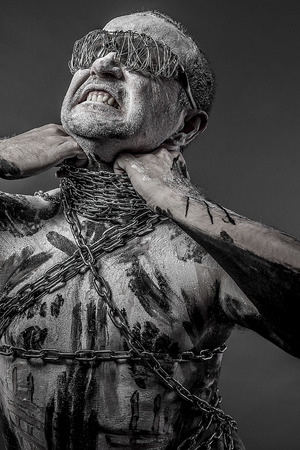 liberate: man with chains and blindfolded concept of prison, without freedom