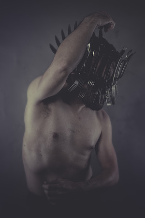 man with crown made of silver forks and knives photo