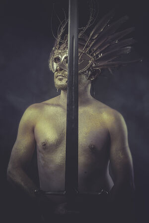 War, man and warrior with painted golden skin, golden feathers mask photo