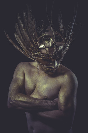 man and warrior with painted golden skin, golden feathers mask photo