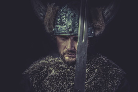 Warning, Viking warrior with a huge sword and helmet with horns photo