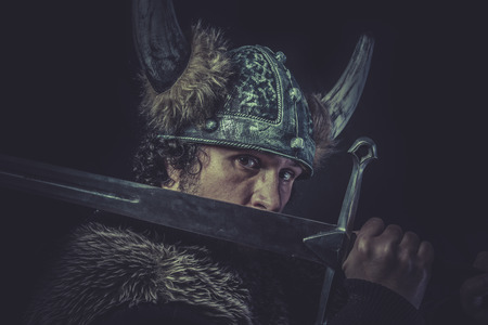 Danger, Viking warrior with a huge sword and helmet with horns photo