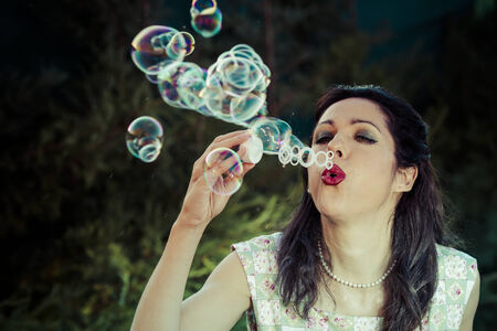 a beautiful woman blowing bubbles. spring season, rural scene photo