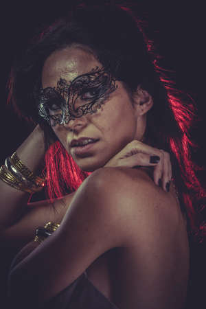 Party brunette woman with golden jewelry and red light on hair photo