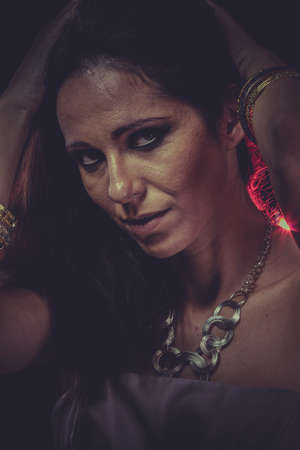 Party night brunette woman with golden jewelry and red light on hair photo