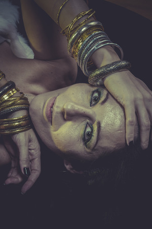 Dark brunette woman with gold and silver jewelry photo