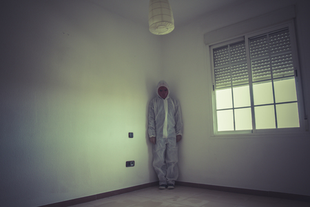 Schizophrenia, nightmare man with red mask in empty room photo