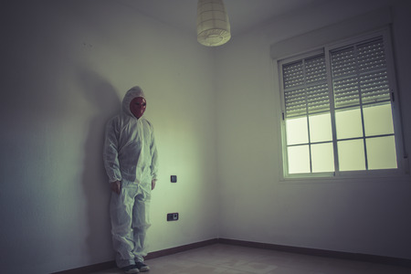 Psychiatrist, nightmare man with red mask in empty room photo