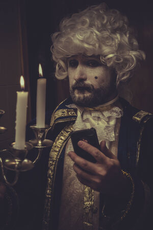 nineteenth: Smartphone Selfie, man with white wig and candlestick nineteenth century Stock Photo