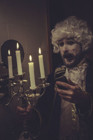nineteenth: Funny Selfie, man with white wig and candlestick nineteenth century Stock Photo