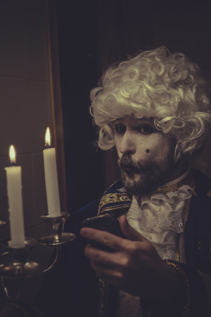 nineteenth: Mobile Selfie, man with white wig and candlestick nineteenth century Stock Photo