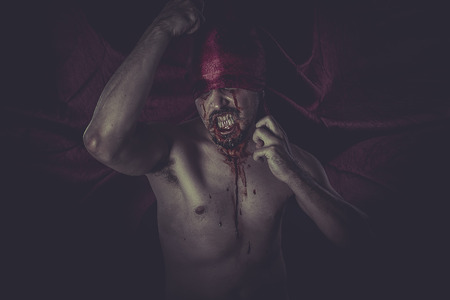 vampire with big teeth and blood in the neck photo