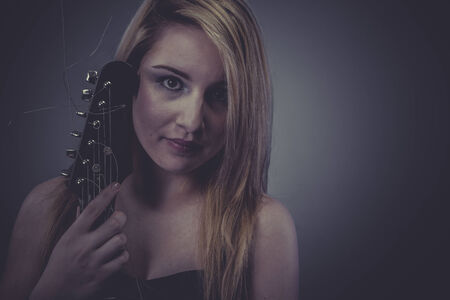 Pop, Beautiful blonde with black electric guitar photo