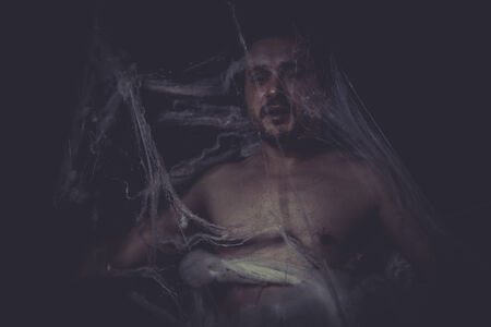 man trapped: Horror, Man trapped in a spider web Stock Photo