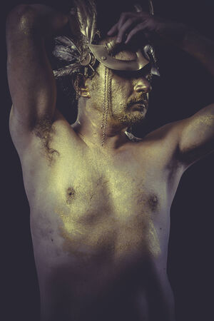 Vogue Man with body painted gold feather mask and steel sword photo