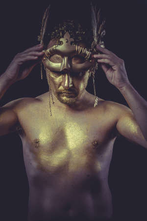 Golden, Man with body painted gold feather mask and steel sword photo