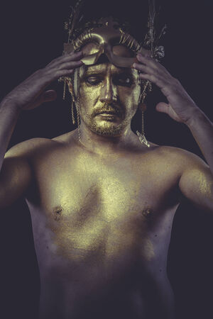Fashion, Man with body painted gold feather mask and steel sword photo