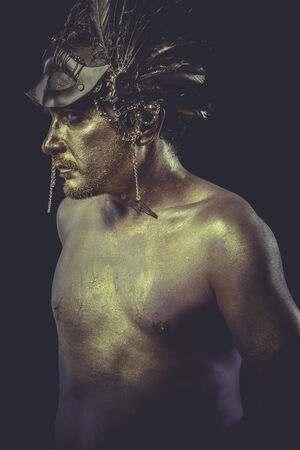 Bronze man with body painted gold feather mask and steel sword photo