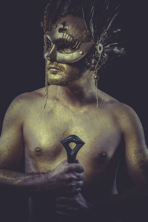 Greek man with body painted gold feather mask and steel sword photo