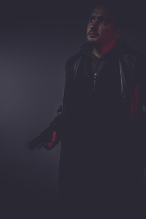 portrait of stylish man with long leather jacket, gun armed photo