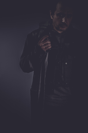 Bodyguard, portrait of stylish man with long leather jacket, gun armed photo