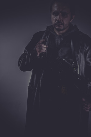 Killer, portrait of stylish man with long leather jacket, gun armed photo