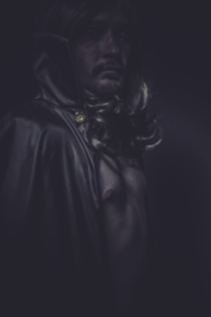 Man dressed in long black cape, vampire photo