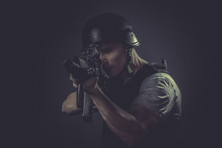 Security  sport player wearing protective helmet aiming pistol ,black armor and machine gun photo