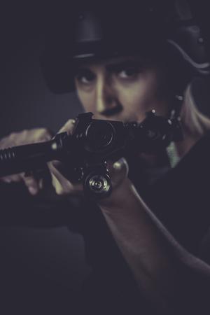 gunfire: Gunfire, paintball sport player wearing protective helmet aiming pistol ,black armor and machine gun