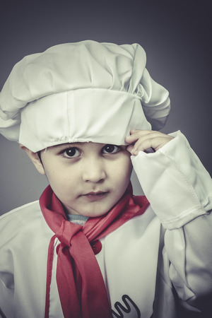 small child dress funny chef, cooking utensils photo