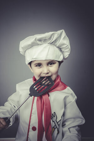 boy dressed as a cook with kitchen utensils photo